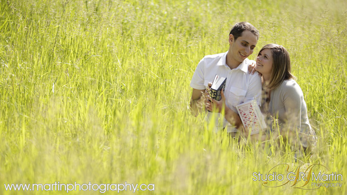 couple in field reading book engagement photos