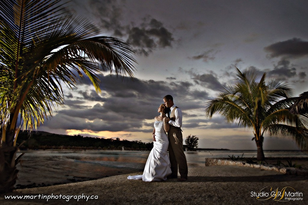 jamaica beach sunset destination wedding -  couple with palm trees - Grand Bahia Principe Jamaica in Runaway Bay
